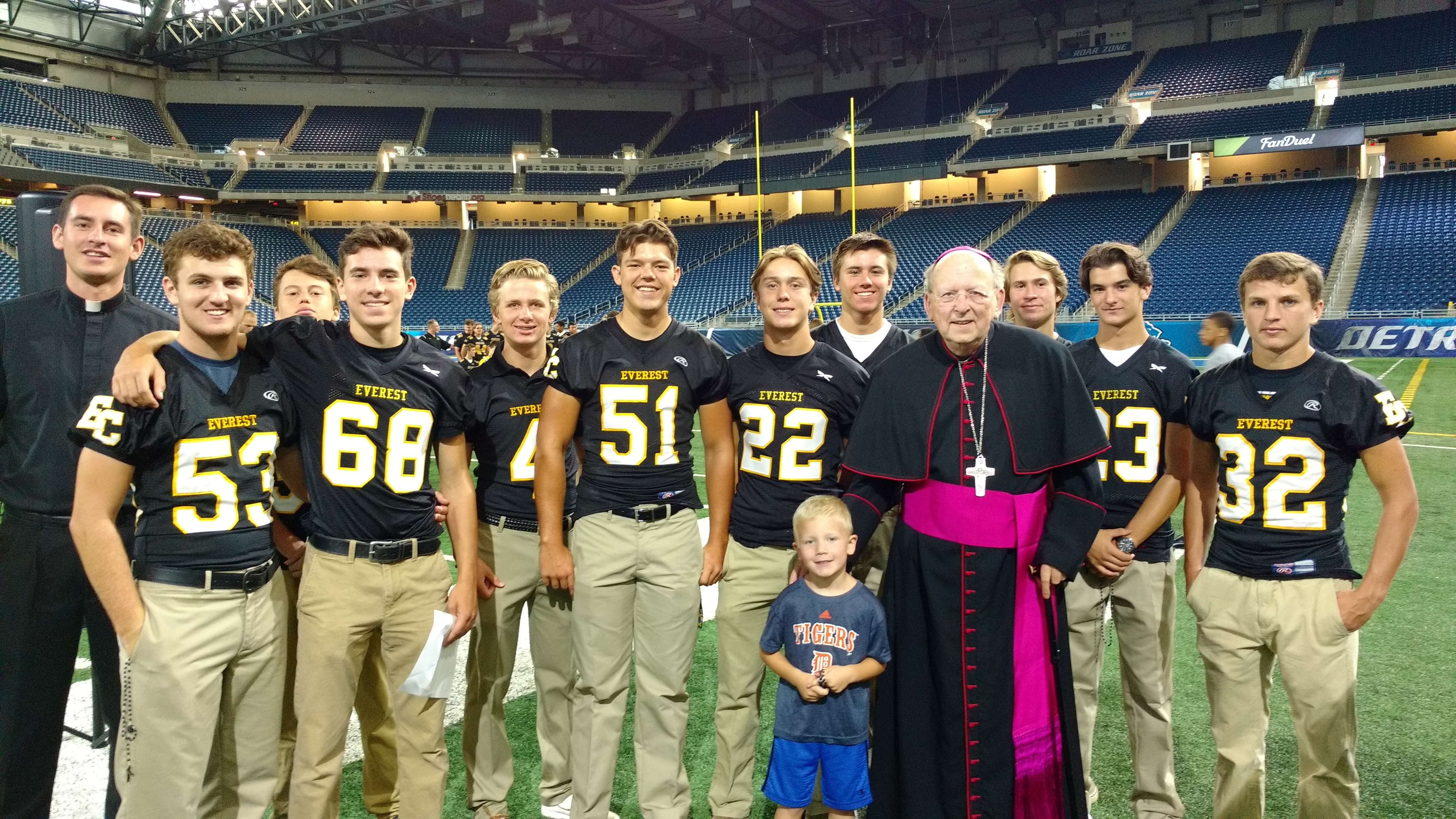 The Everest Collegiate High School Football team stands on Ford Field with Bishop Francis Rice during the annual Rosary Rally. On the left is Fr. Benjamin O'Loughlin LC and in front of Bishop Rice is Coach Mike Pruchnicki's son.