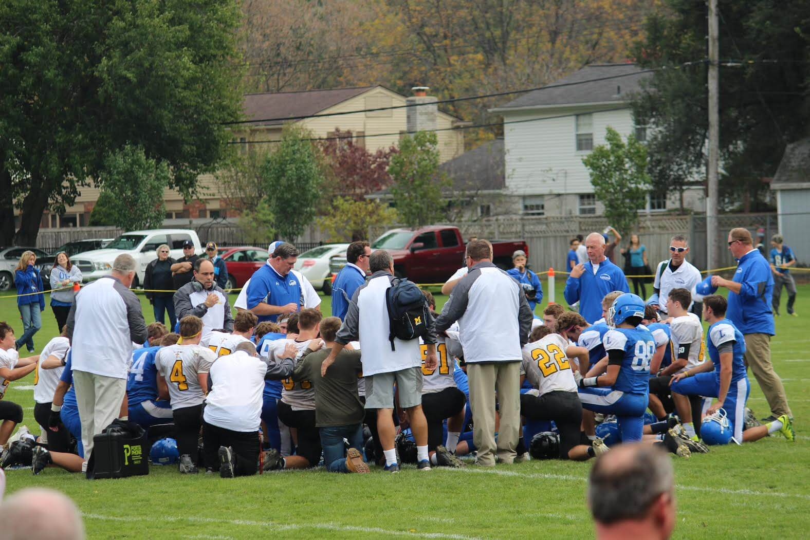 Both teams pray together after the game.