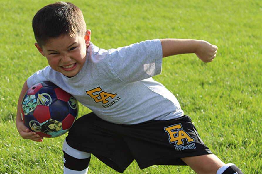 Early years student playing soccer