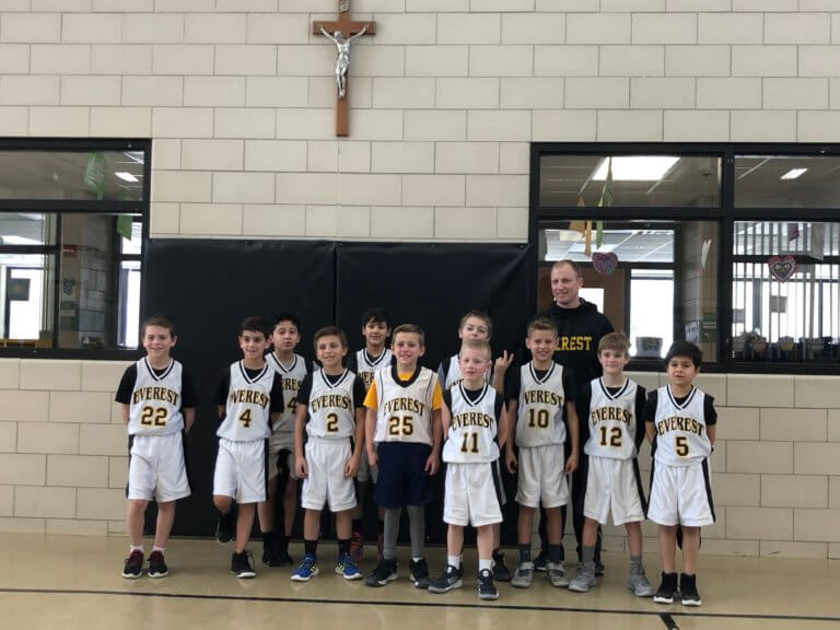 Boys elementary basketball team picture with the coach in the gym