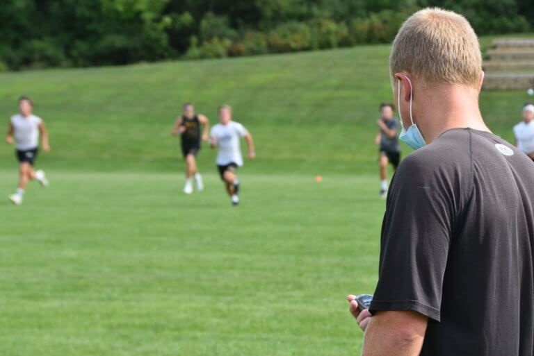 Football camp coach with stopwatch